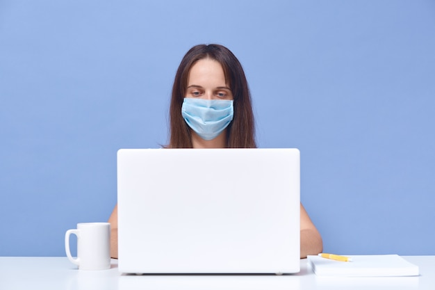 Adorable dark haired woman working on studying online, sitting at white desk near opened lap top and cup, female wearing white t shirt and protective medical mask. freelancer. Free Photo