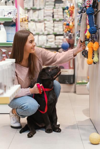Adorabile cane con il proprietario presso il negozio di animali Foto Gratuite