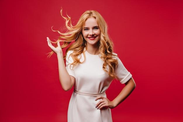 Очаровательная европейская девушка, выражающая волнение. удивительная блондинка в белом платье. Бесплатные Фотографии