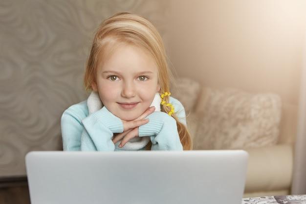 開いているラップトップの前に座っているポニーテールのブロンドの髪を持つ愛らしい一年生の女の子 無料写真