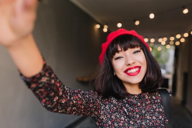 Очаровательная французская брюнетка со стильным макияжем и короткой прической, развлекаясь с камерой на размытом фоне. довольно темноволосая молодая женщина в винтажной одежде делает селфи и счастливо улыбается Бесплатные Фотографии