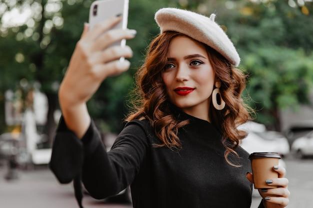 Donna adorabile dello zenzero in berretto che fa selfie all'aperto. signora attraente che beve caffè per strada. Foto Gratuite