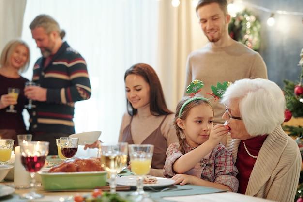 Очаровательная девушка дает прабабушке маленький помидор, сидя за праздничным столом с молодыми и зрелыми парами Premium Фотографии