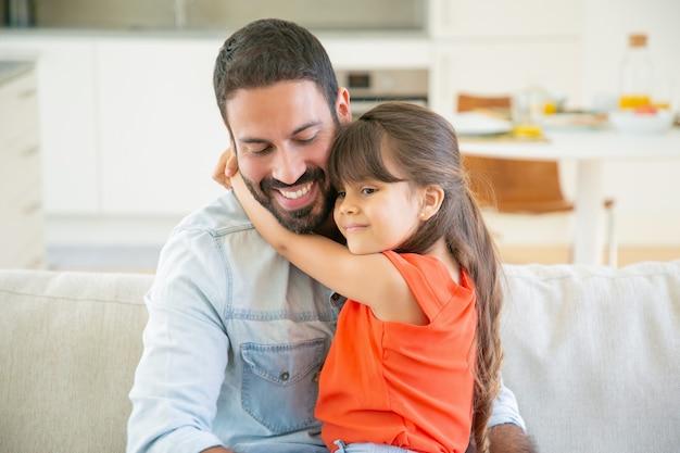 愛らしい少女が彼の膝の上に座っている間彼女のお父さんを抱き締めます。 無料写真
