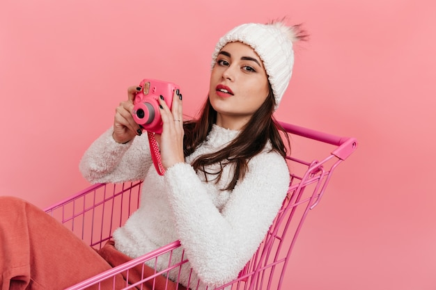 スーパーマーケットのトロリーに座って、孤立した壁にポーズをとってピンクのカメラを手に白い冬の服を着た愛らしい女の子。 無料写真