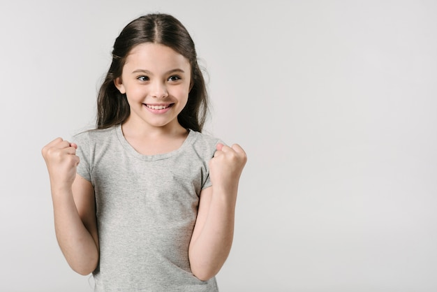 Adorable girl rejoices victory in studio Free Photo