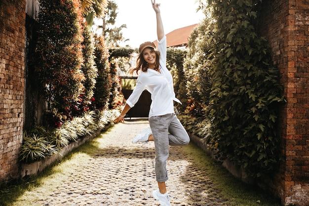 사랑스러운 소녀는 평화의 표시를 보여줍니다. 대형 셔츠와 바지 아이비와 꼬인 울타리 경로에 미소로 점프하는 여자. 무료 사진