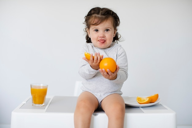 Adorable girl sitting and showing her oranges Free Photo