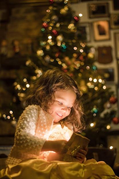 Adorabile ragazza sorridente e guardando il suo regalo di natale Foto Gratuite