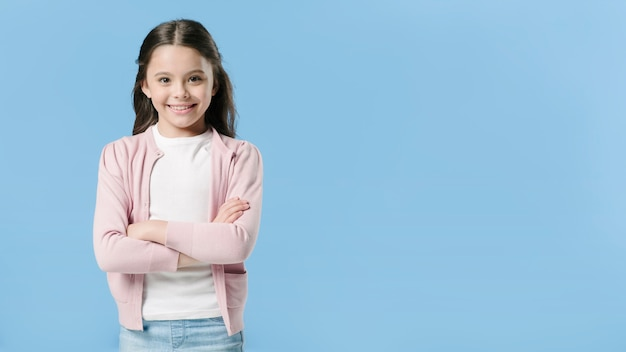 Adorable girl standing in studio and smiling Free Photo