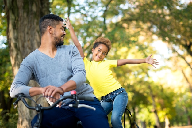Adorable girl with raised arms and father on a bicycle enjoying in the park Free Photo