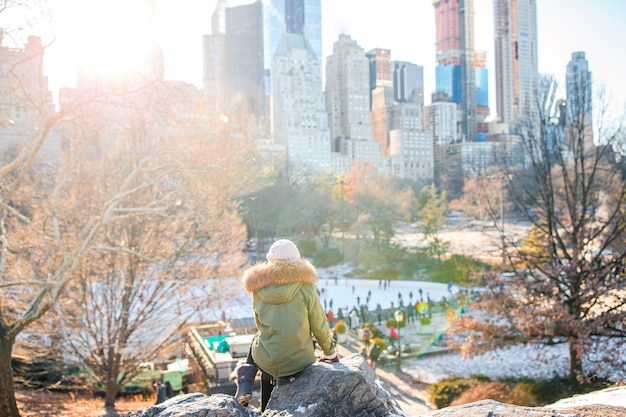 Adorable girl with view of ice-rink in central park on manhattan in new york city Premium Photo