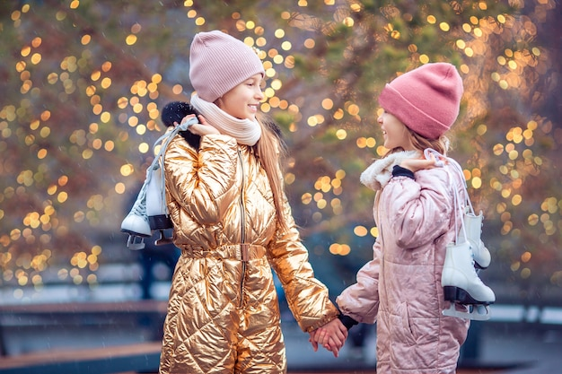 Adorable girls skating on ice rink outdoors in winter snow day Premium Photo