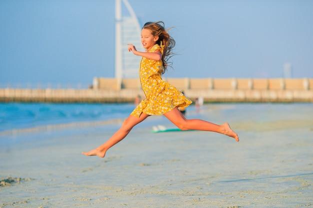 Очаровательная счастливая маленькая девочка на белом пляже на закате Premium Фотографии