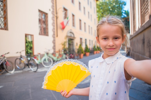 Adorable happy little girl taking selfie outdoors in european city. portrait of caucasian kid enjoy summer vacation in old city Premium Photo