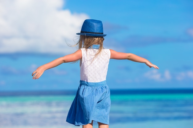 Adorable happy smiling little girl in hat on beach vacation Premium Photo