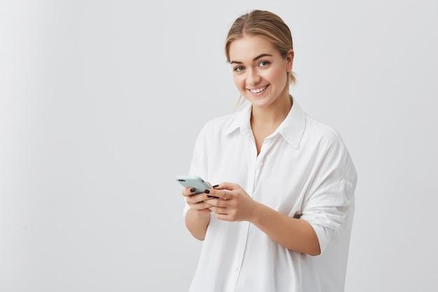 Прелестная хипстерская кавказская женщина со светлыми волосами проверяет свою новостную ленту или сообщения в социальных сетях, используя бесплатный wi-fi на мобильном телефоне, улыбается, позирует Бесплатные Фотографии