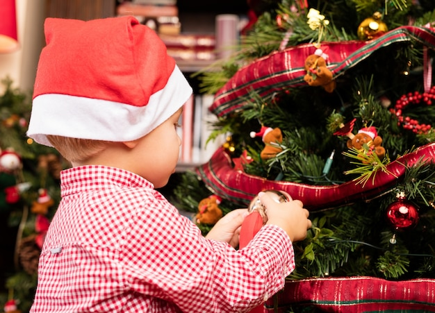 Adorable kid decorating a tree on christmas Free Photo