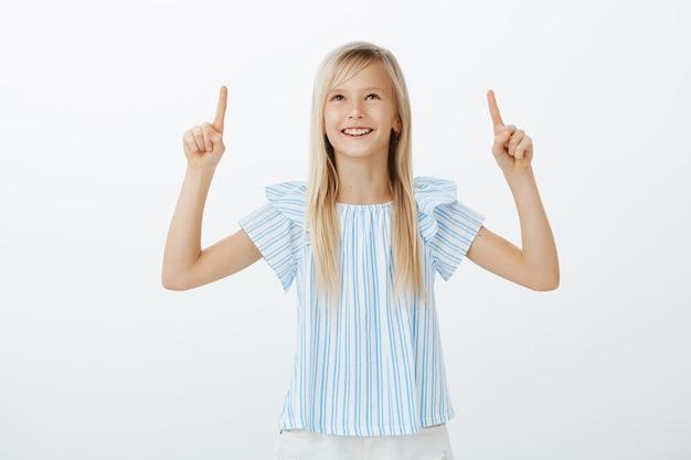 友達と雲の形を議論する愛らしい子供。ブロンドの髪を持つ創造的な幸せな若い女の子の肖像画、肯定的な感情から広く笑みを浮かべて、見上げて人差し指で上向き 無料写真