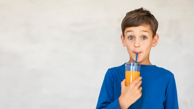 いくつかのオレンジジュースを飲むかわいい子供 無料写真