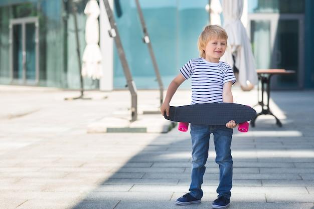 Очаровательны малыш на открытом воздухе. милый довольно веселый ребенок, держа скейтборд случайные мальчик на летнее время кататься на коньках на скейтборде. Premium Фотографии