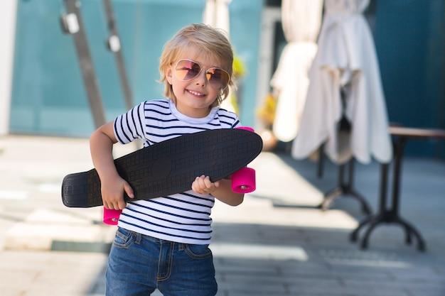 Очаровательны малыш на открытом воздухе. милый милый ребенок в солнечных очках усмехаясь на камере. вскользь мальчик на временени катаясь на коньках на скейтборде. Premium Фотографии