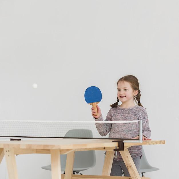 Прелестный ребенок играет в пинг-понг в помещении Бесплатные Фотографии