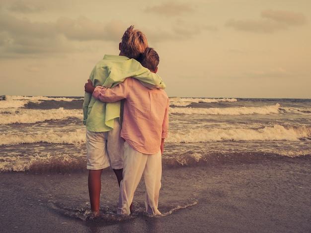 愛らしい子供たちはビーチでお互いをハグし、海の美しい景色を楽しみます 無料写真
