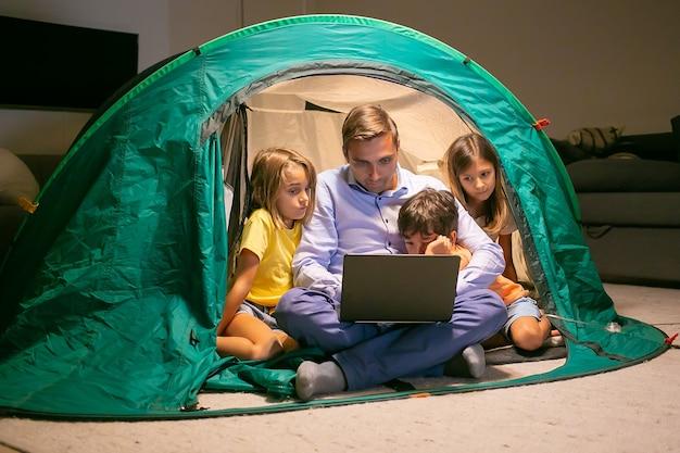 Очаровательные дети отдыхают с отцом в палатке дома и смотрят фильм на портативном компьютере. счастливые дети и любящий папа, сидя в палатке со светом. детство, семейное время и концепция выходных Бесплатные Фотографии