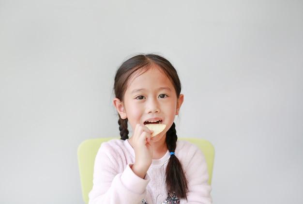 Adorable little asian child girl eating crispy potato chips on white. Premium Photo