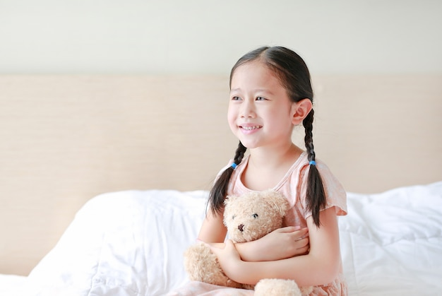Adorable little asian girl embracing teddy bear while sitting on the bed at home. Premium Photo