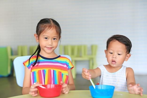 コーンフレークとミルクで穀物を食べる愛らしい小さなアジアの妹と彼女の弟 Premium写真