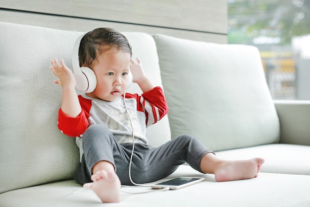 Adorable little baby boy sitting on sofa and listening music at headphones by smartphone Premium Photo