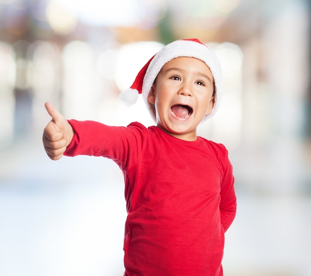 Adorable little boy showing a positive sign Free Photo