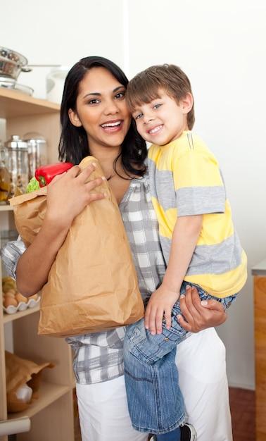 Очаровательный маленький мальчик, распаковывающий продуктовый портфель с матерью Premium Фотографии