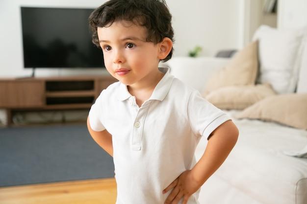 Adorabile ragazzino in camicia bianca in piedi con le mani sui fianchi in soggiorno Foto Gratuite