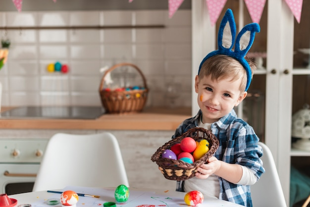 Adorable little boy with bunny ears holding a basket with eggs Free Photo