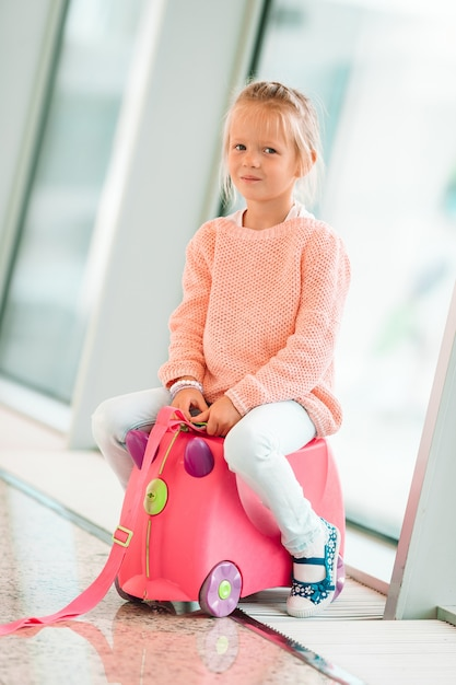 Adorable little girl in airport with her luggage waiting for boarding Premium Photo
