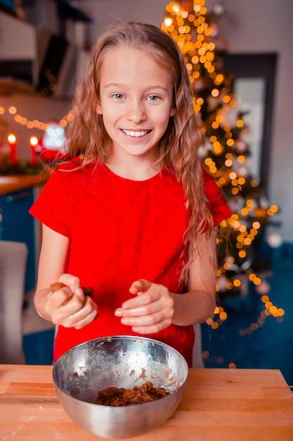 Adorable little girl baking christmas gingerbread cookies Premium Photo