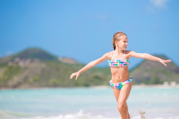 a056b3bfc62d Adorable little girl at beach having a lot of fun in shallow water Premium  Photo