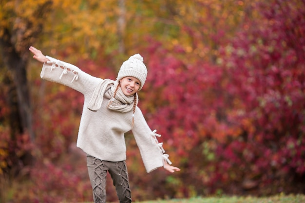 Adorable little girl at beautiful autumn day outdoors Premium Photo