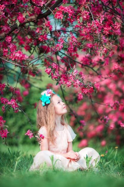 Adorable little girl in beautiful blooming apple garden outdoors Premium Photo