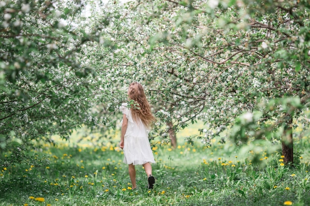 Adorable little girl in blooming apple garden on beautiful spring day Premium Photo