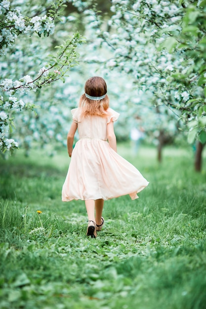 Adorable little girl in blooming apple tree garden on spring day Premium Photo