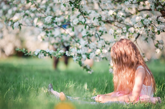 Adorable little girl in blooming cherry tree garden on spring day Premium Photo