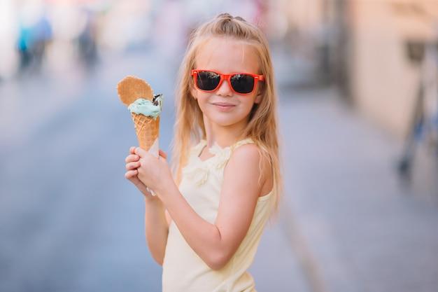 여름에 야외에서 아이스크림을 먹는 사랑스러운 작은 소녀. 프리미엄 사진