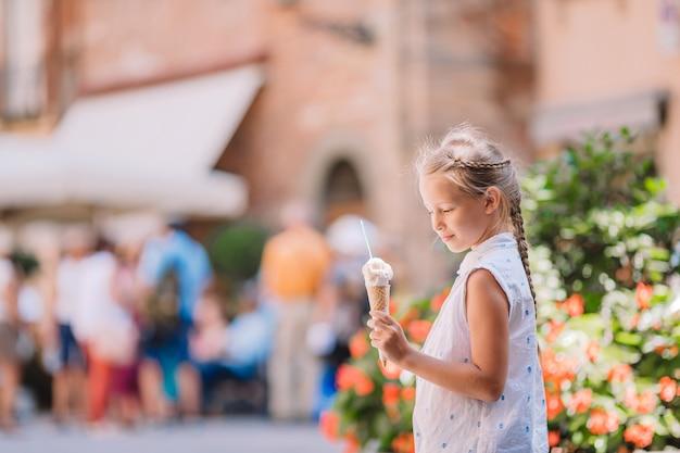 아이스크림을 먹는 사랑스러운 어린 소녀 프리미엄 사진