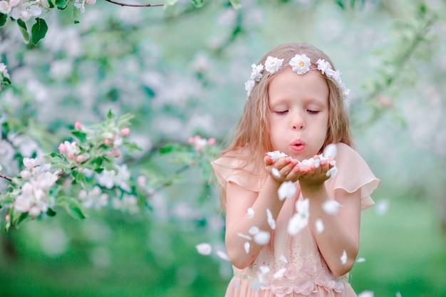 Adorable little girl enjoying spring day in apple blooming garden Premium Photo