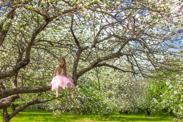 Adorable little girl have fun in blossoming apple orchard Premium Photo