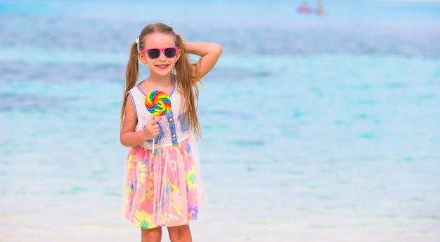 Adorable little girl have fun with lollipop on the beach Premium Photo